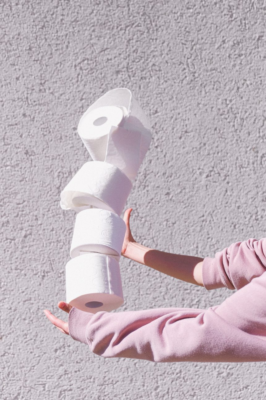 woman in pink jumper holding stack of toilet paper